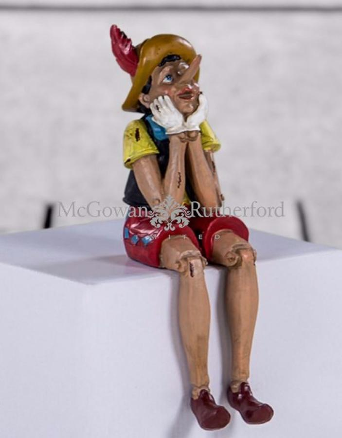 Antiqued sitting Pinnochio figure