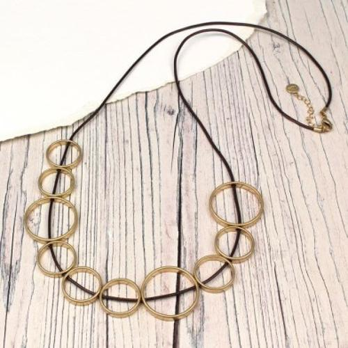 Worn gold mixed hoops on brown cord necklace