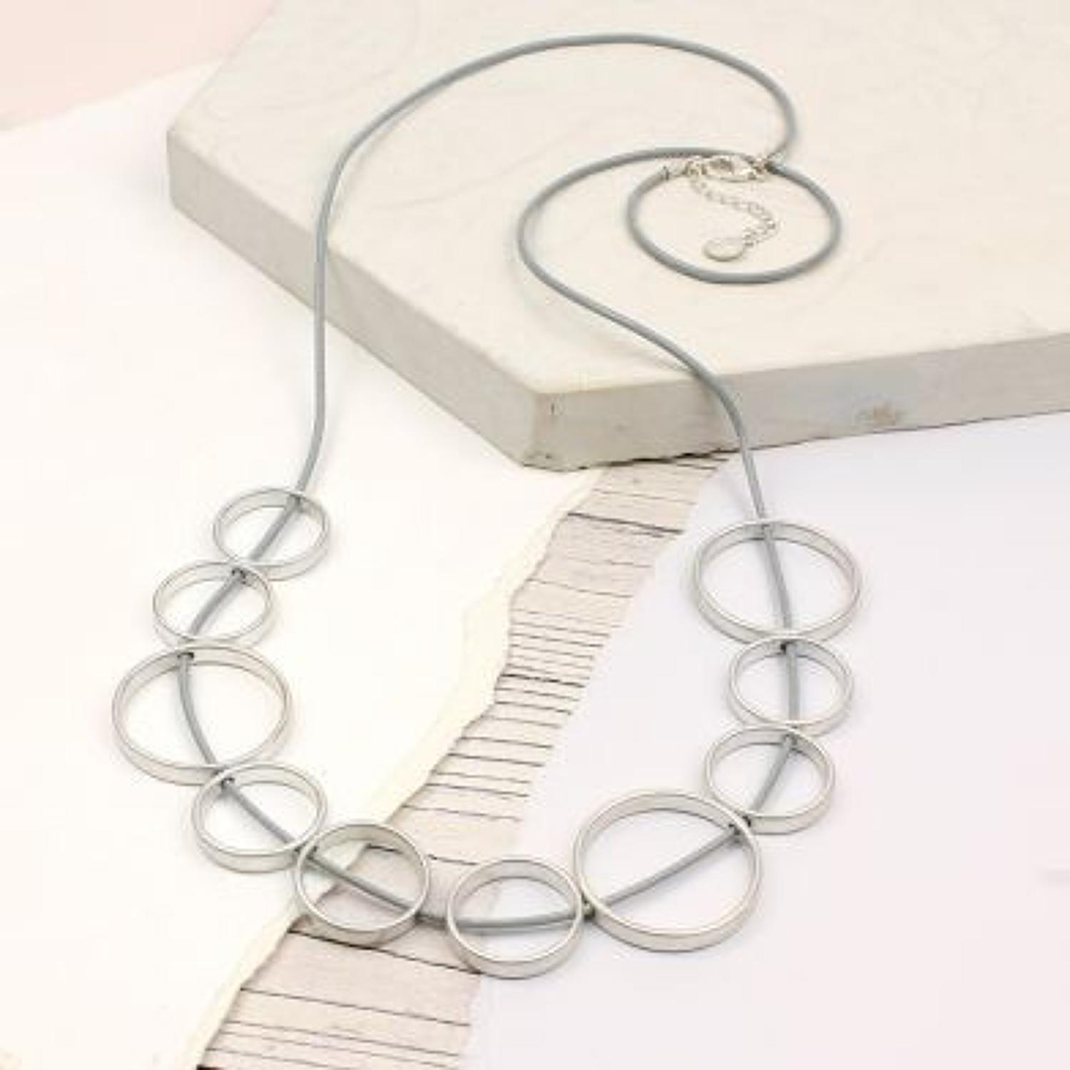 POM - Large worn silver mixed hoops on grey cord necklace