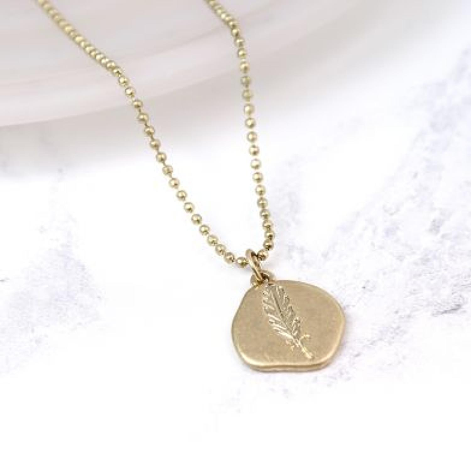 POM - Worn gold organic disc feather necklace