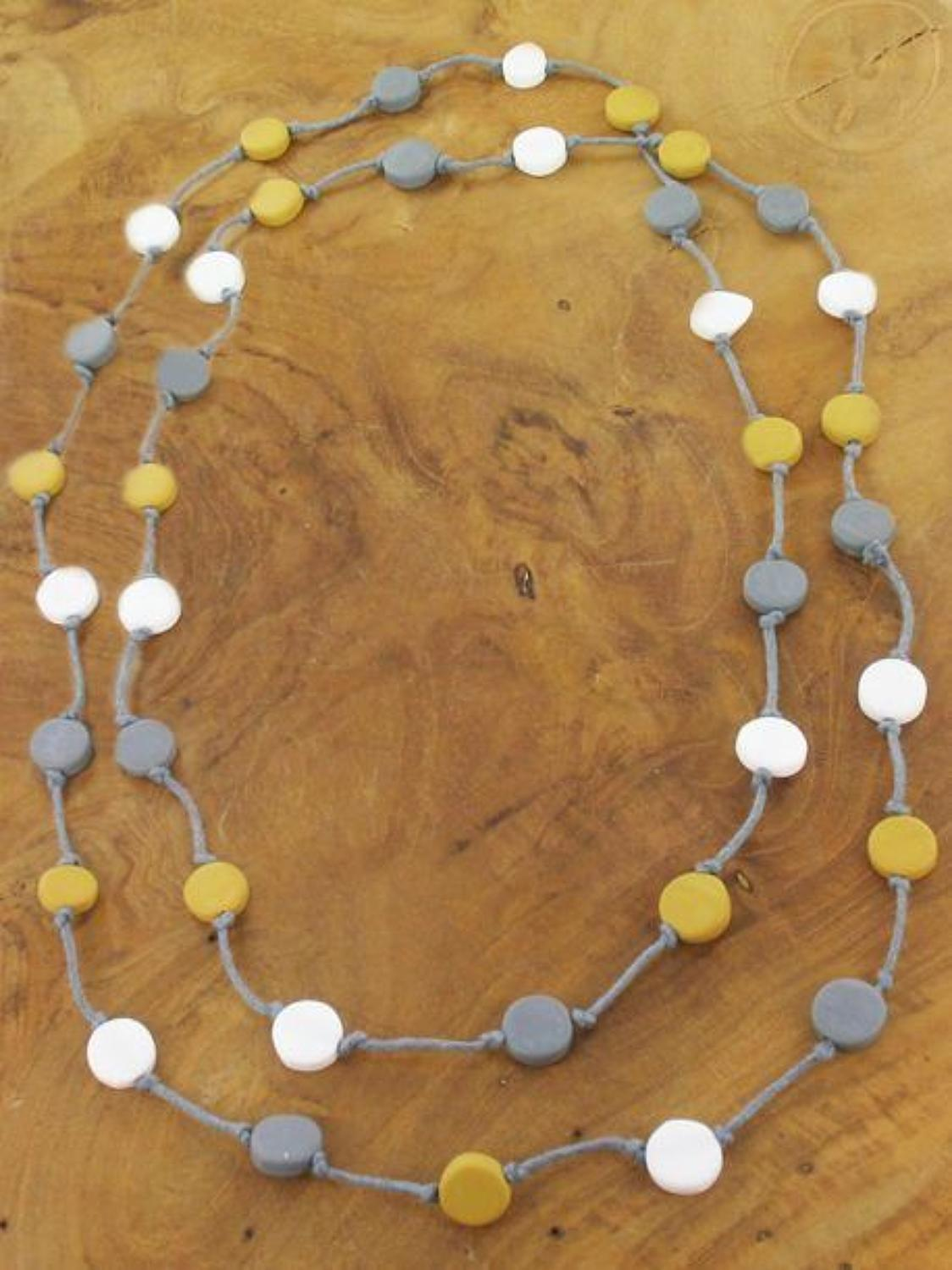 Suzie Blue-Long resin disc necklace on grey string-Mustard/Grey/white